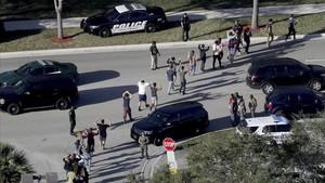Evacuación de estudiantes con los brazos en alto a la salida del instituto Marjory Stoneman Douglas, en Parkland (Florida), el 14 de febrero.