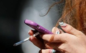 Una menor de edad con un cigarrillo en la mano.