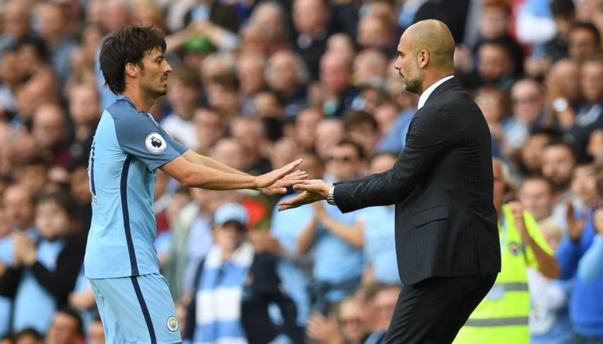 Guardiola felicita a Silva durante un partido del Manchester City en la Premier.