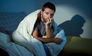 Hombre sentado en el sofá por la noche con miedo.