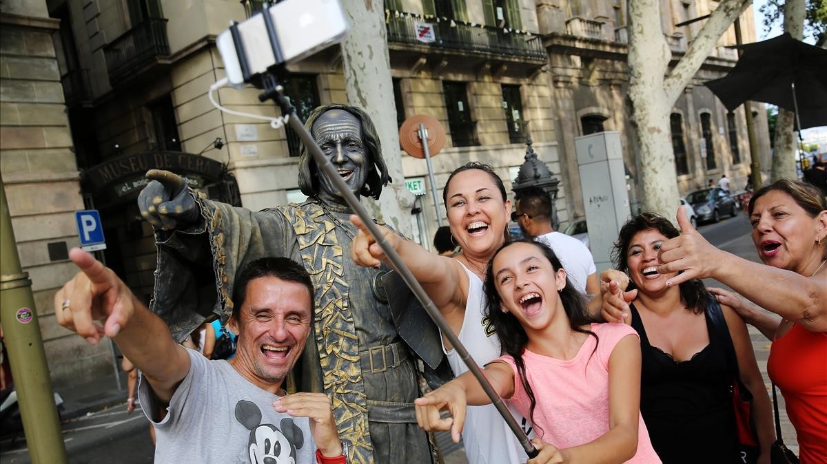 Un grupo se hace un selfi con una estatua humana de la Rambla de Barcelona, este martes.