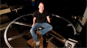 Jeff Bezos encima de uno de los engranajes de su reloj milenario