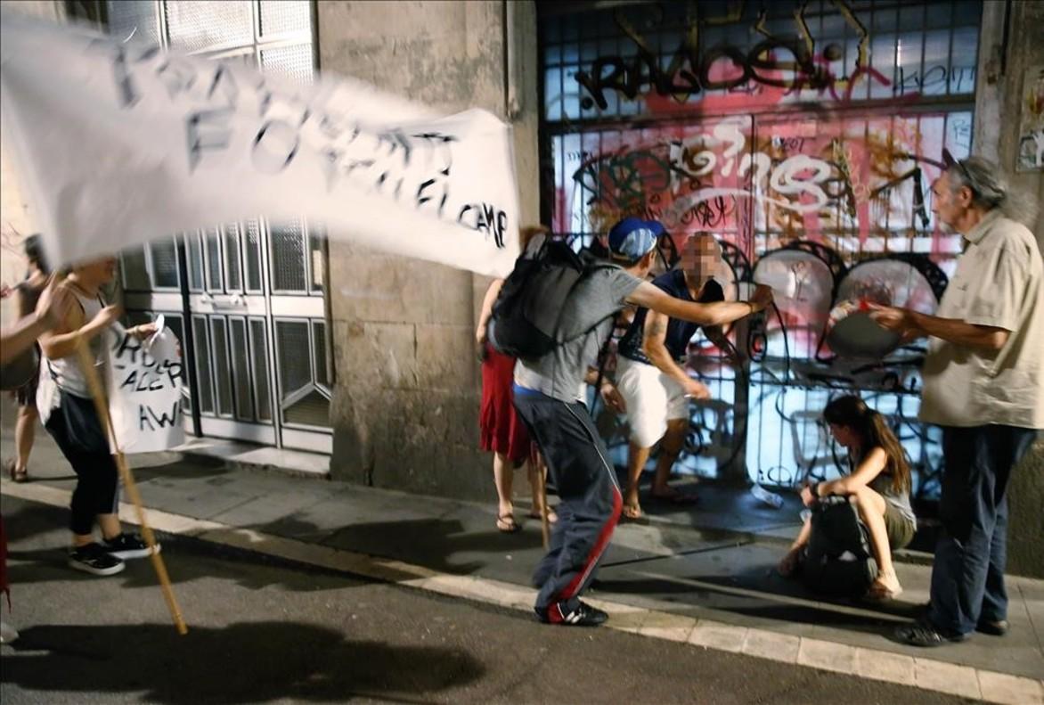 Vecinos increpan a dos personas que se pinchan en la calle de En Roig en plena cacerolada de protesta contra los narcopisos del Raval, este martes.