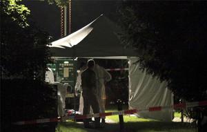 Los forenses examinan un cadáver, tendido en el suelo, cerca del lugar de los hechos.