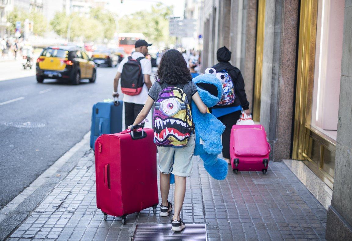 Una familia de turistas arrastrando sus maletas y resto de enseres a su llegada a Barcelona.