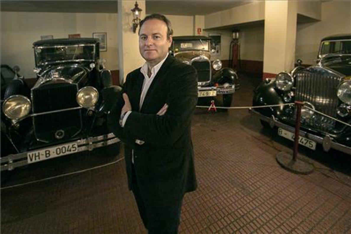 Javier Tulla posa rodeado de automóviles clásicos y de colección en la sede del Antic Car Club de Catalunya.