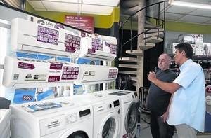 Un vendedor asesora a un cliente en una tienda de electrodomésticos.