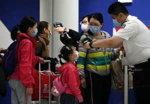 Passengers arriving into Hong Kong International Airport get their temperature checked by a worker using an infrared thermometer, following the coronavirus outbreak in Hong Kong, China, February 7, 2020. REUTERS/Hannah McKay
