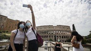 Dos jóvenes se hacen un 'selfie' frente al Coliseum, hoy lunes en Roma.