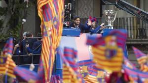 Suárez e Iniesta, junto a las copas, durante la rúa del Barça.
