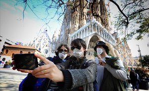 Turistas con mascarilla junto a la Sagrada Família.
