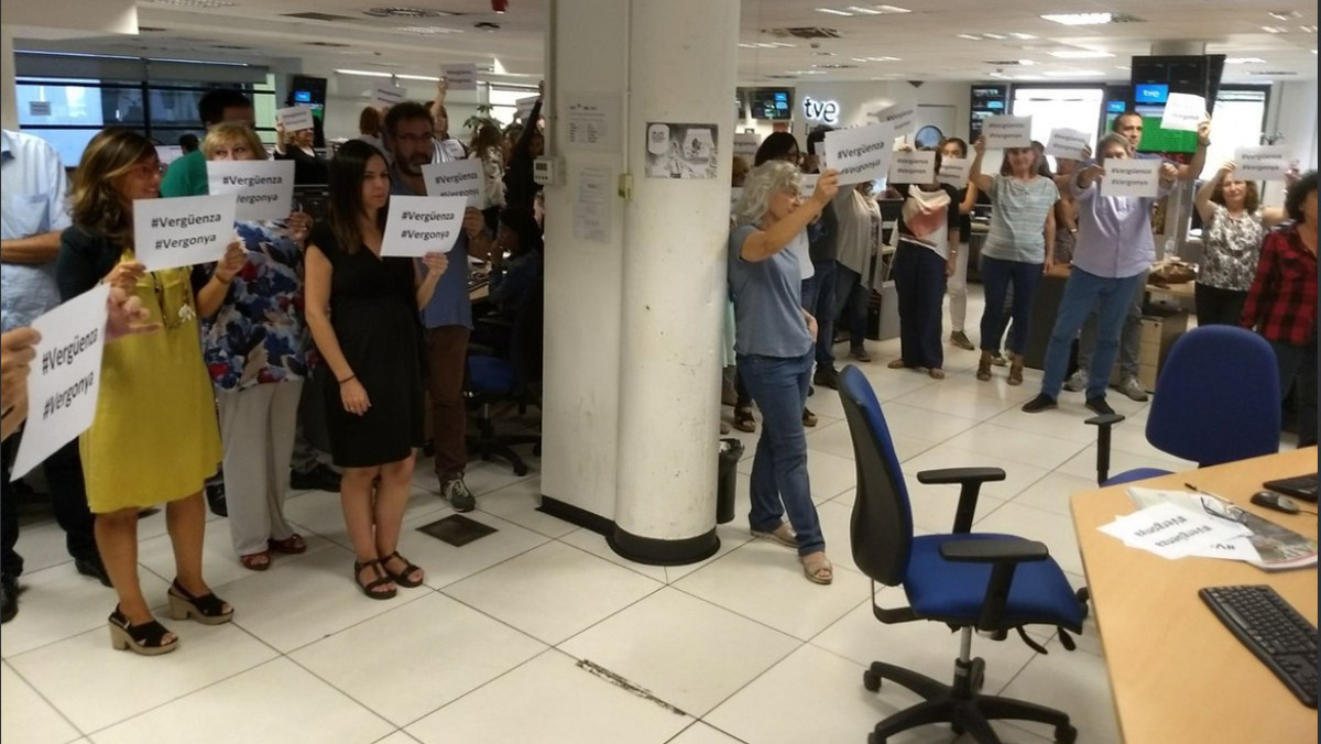 Imagen de la redacciónde TVE con periodistas protestando por la cobertura del 1-O con carteles de vergüenza y vergonya.