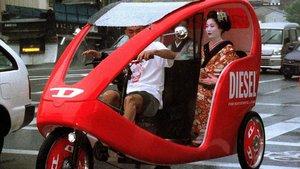 Una geisha se desplaza en un taxi triciclo por Kioto.