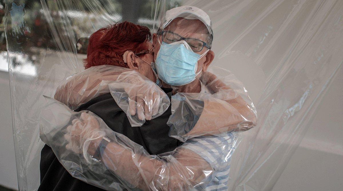 Una interna en una residencia de mayores abraza a un familiar a través de un plástico habilitado para que tengan su primer contacto desde hace tres meses, en València, el 17 de junio.
