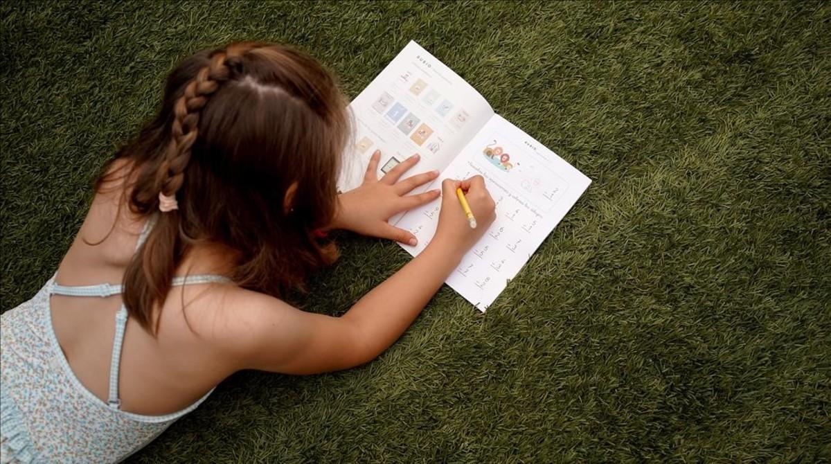 Una niña de siete años estrena sus vacaciones, el viernes en Madrid, haciendo ejercicios en un cuaderno Rubio.