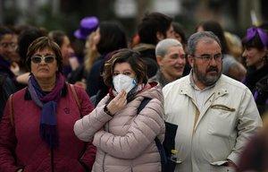 Una participante en la manifestación del 8M en Madrid se protege con una mascarilla por el riesgo de coronavirus.