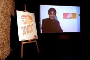 Videoconferencia de Puigdemont, junto a un cartel de Junts per Catalunya.