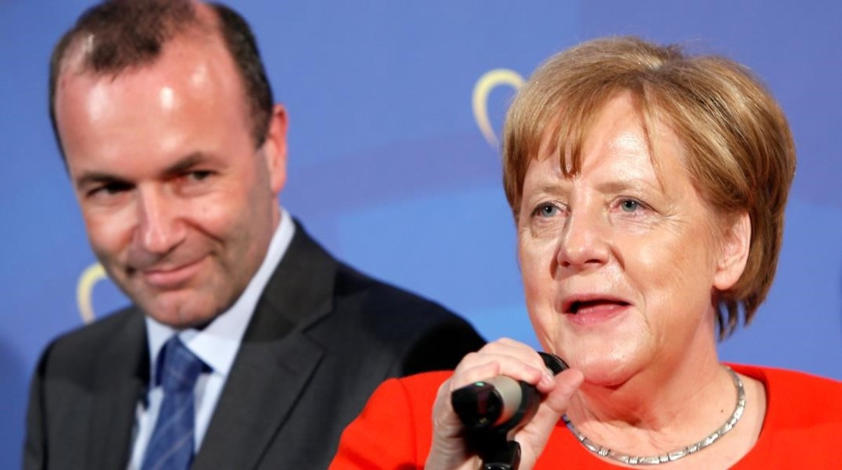 Manfred Weber, presidente del grupo del PPE en el Parlamento Europeo, escucha a la cancillera Angela Merkel, el 6 de junio del 2018.