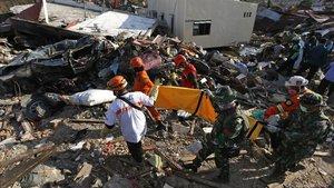 Equipos de rescate sacan de los escombros a una víctima del terremoto.
