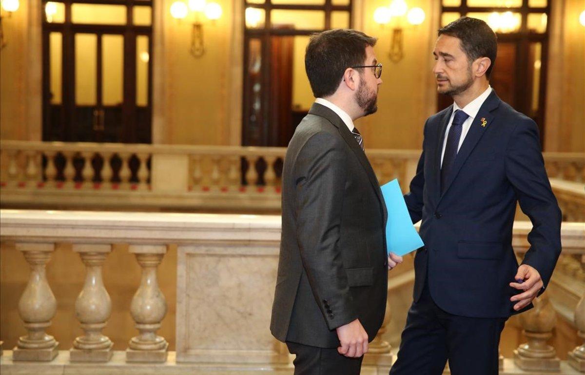 El 'conseller' de Territori,DamiàCalvet, a la derecha, habla con el vicepresidente y'conseller' de Economia, Pere Aragonés, esta mañana en el Parlament.