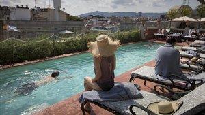 Clientes en la piscina situada en la azotea del Hotel Palace, en Barcelona.