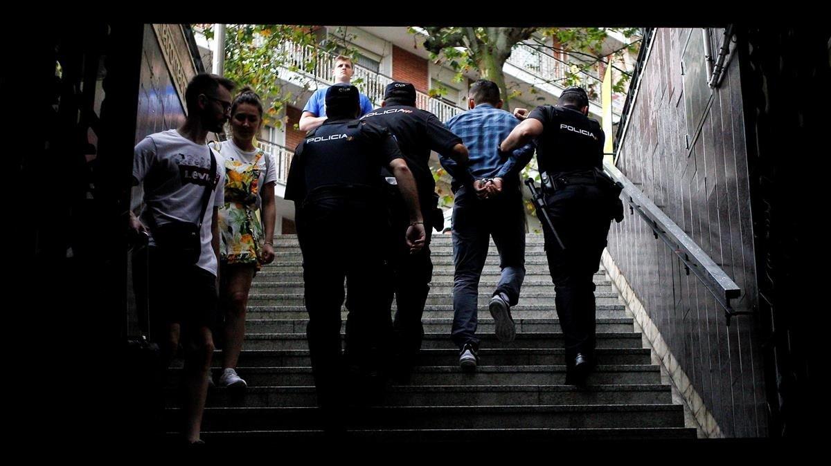 Dos policías se llevan a un detenido en el metro de Barcelona, en agosto pasado.