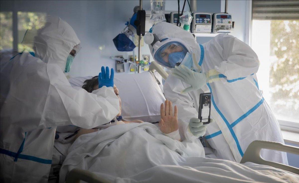 Médicos de la UCI delHospital Clinico de València, dentro de uno de los boxes de la unidad.