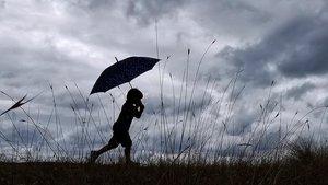 Un nino se resguarda de la lluvia con la ayuda de un paraguas en Mino (A Coruña), el pasado agosto.