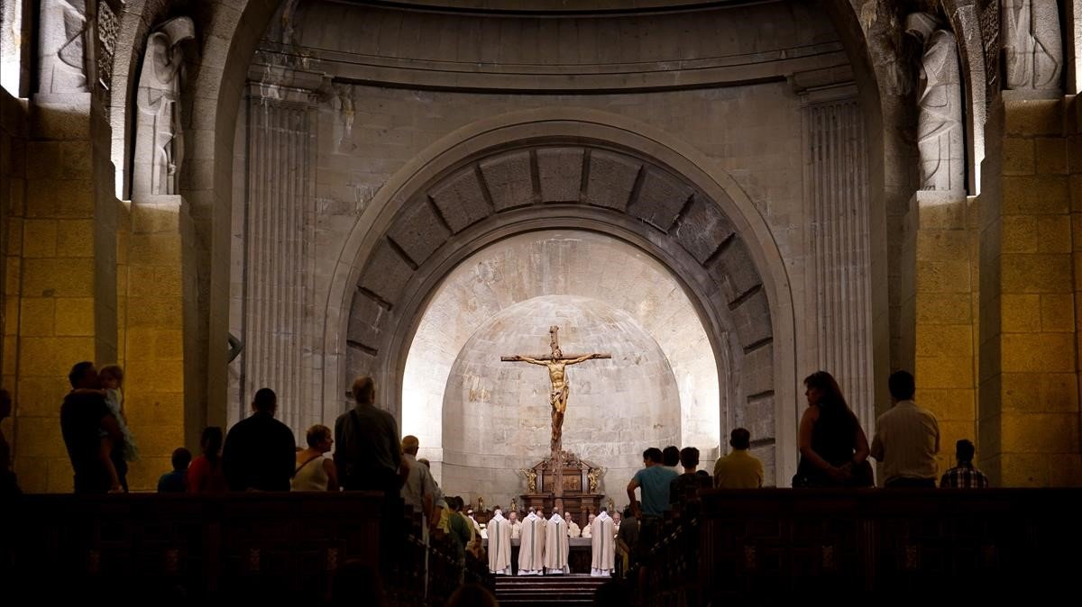 Los monjes benedictinos concelebran una de sus misas diarias en el altar junto al que se encuentra la tumba de Francisco Franco.