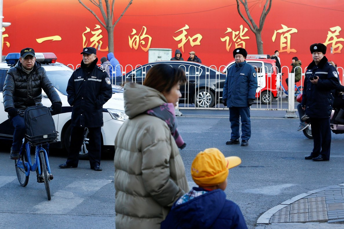 Police watch as a woman and a child leave a primary school that was the scene of a hammer attack in BeijingChinaREUTERS Thomas Peter