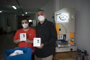 Óscar Sánchez (derecha) y Eric López, operario, junto a la máquina que les permite dar un empuje a su empresa Gari Gimeno con la fabricación de mascarillas FFP2.