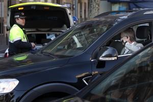 Un Guardia Urbano multa a un conductor en Barcelona.