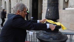 Alberto Fernandez Diaz retira lazos amarillas de las farolas de delante del Ayuntamiento.