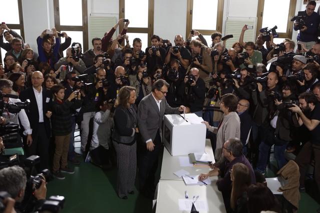 Artur Mas vota junto a su esposa, rodeado de cámaras y fotógrafos.