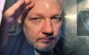 Assange, observa desde la ventana de una furgoneta policial, en Londres, el año pasado.