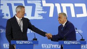 Benny Gantz (izquierda) y Yair Lapid se estrechan la mano mientras anuncian una declaración conjunta.