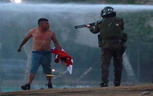 Un polícia en Chile apunta con su arma a un manifestante.