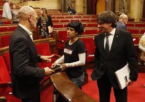 Carles Puigdemont observa a la diputada de la CUP Anna Gabriel y al 'conseller' Romeva, en el Parlament.
