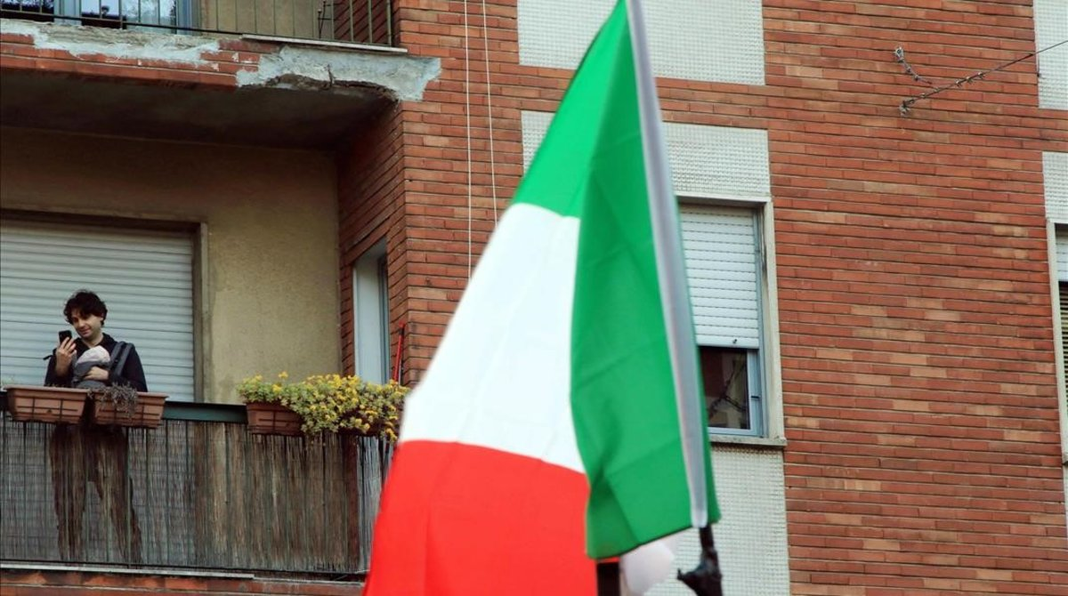 Un ciudadano milanés con su bebé en su balcón.