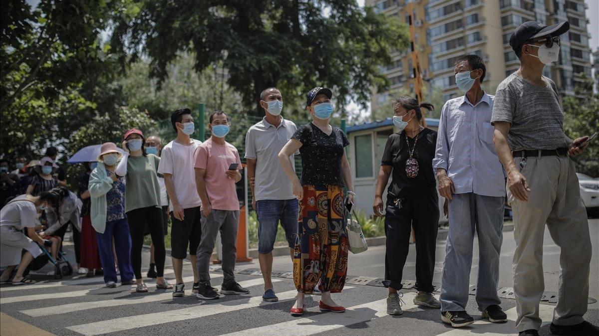 Cola de habitantes de Pekín para hacerse el test del covid-19 tras el último brote en un mercado de la capital china.