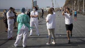 Un corredor aplaude a personal sanitario en el paseo marítimo barcelonés.