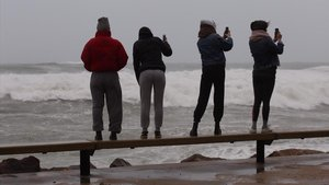 Cuatro jóvenes miran,de forma imprudente,el fuerte oleaje de la playa en Sant Antoni de Calonge.