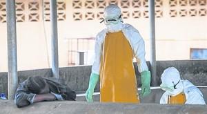 Dos sanitarios se dirigen a recoger el cadáver de una fallecida por ébola en Monrovia.
