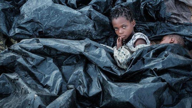 Enia Joaquin Luis se despierta junto a su hermana Luisa bajo los plástico para protegerse de la lluvia mientras se refugian en las gradas del Ring Ring en Buzi Mozambique.