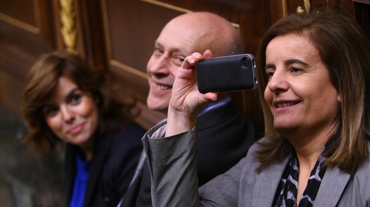 La exministra Fátima Báñez hace una foto con su móvil en el Congreso junto al exministro José Ignacio Wert y la exvicepresidenta Soraya Sáenz de Santamaría.