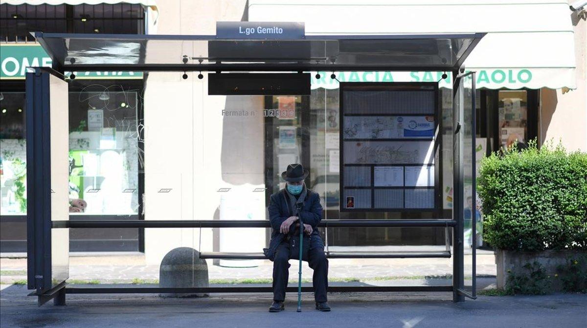 Un hombre en una parada de autobús de Milán.