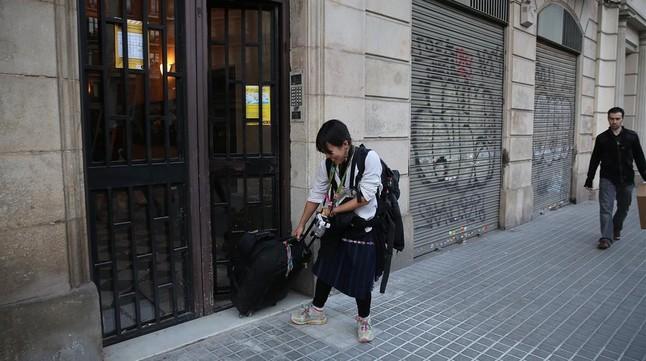 Una turista sale de un apartamento turístico en el Eixample.
