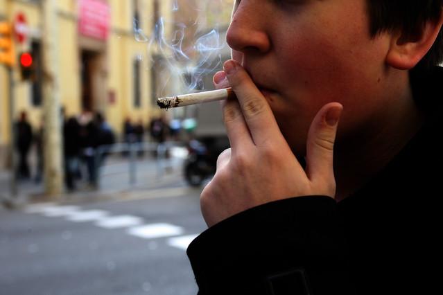 Un joven fumando un cigarro.