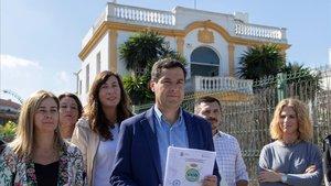 El líder del PP andaluz, Juan Manuel Moreno, muestra frente al club Don Angelo de Sevilla el atestado de la Guardia Civil.