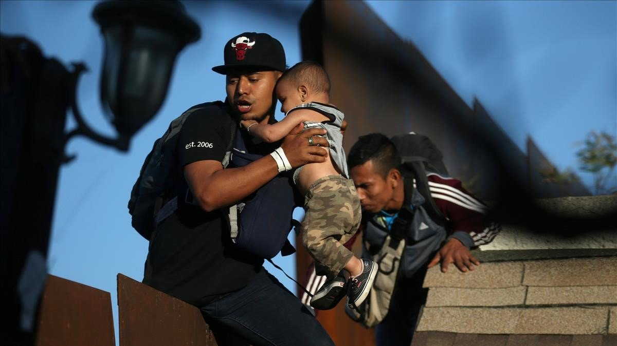 Los migrantes de la caravana intentan saltar el muro desde Tijuana a EEUU.